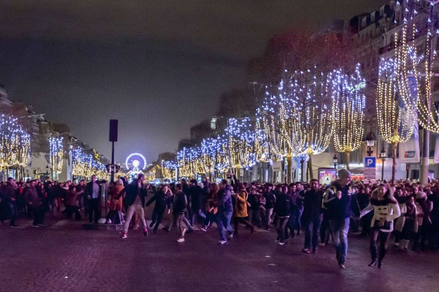 People gather on the Champs-Elysees avenue before celebrating the New Year in Paris on Dec 31, 2015.