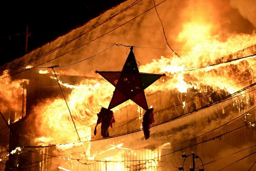 A Christmas decoration is pictured as a huge fire rages through a slum area in Manila on Jan 1, 2016. Nearly 300 homes were destroyed in the early New Year's Day fire, according to local media reports.