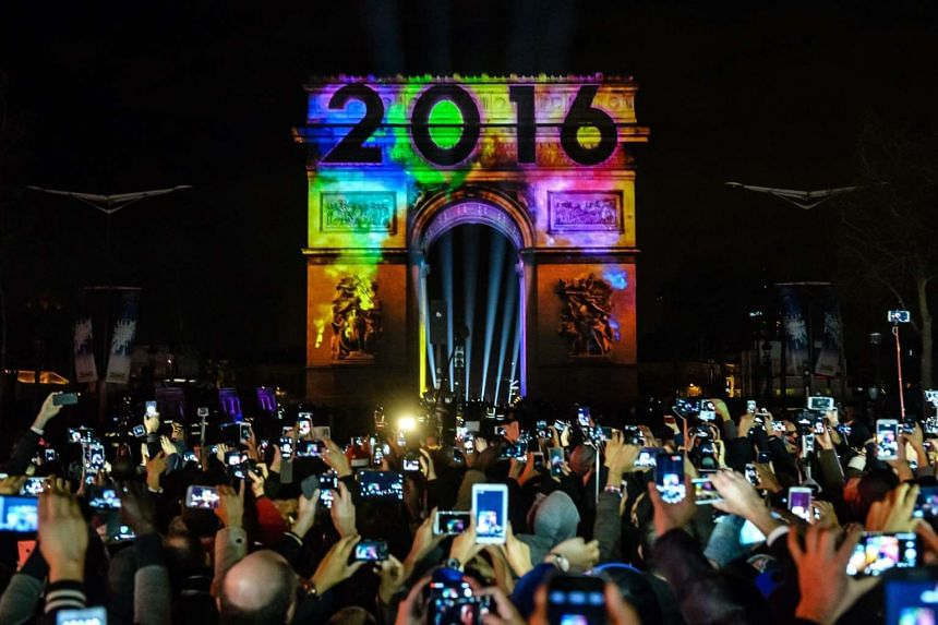People gather on the Champs-Elysees to watch the New Year video display on the Arc de Triomphe in Paris, France.