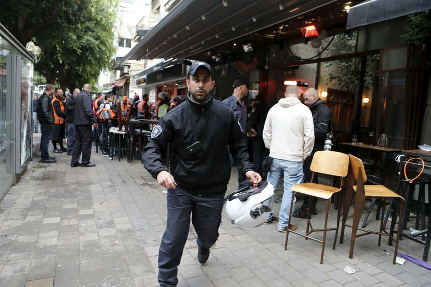 A policemen runs at the scene of a shooting incident in Tel Aviv on Jan 1, 2016.