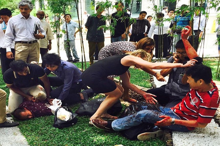 Two passers-by (far left) helped to pin down Arun while others attended to Mr Kang Tie Tie (left), who was bleeding profusely after being stabbed in the robbery in Raffles Place on Nov 14, 2014. Arun was yesterday sentenced to 12 years' jail and 24 s