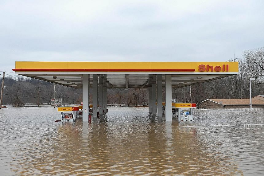 """A petrol station is partly submerged on Route 141 in Fenton, Missouri. Water rose to the rooftops of homes and businesses in the state, with Governor Jay Nixon calling the flooding """"historic and dangerous""""."""