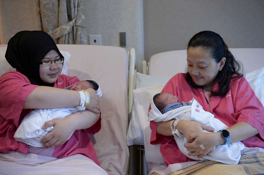 Khairunnisa Anwar (left) and Tee Bee Ling hold their newborn sons Khairy Rusyaidy and Ansley Soong at KK Women's and Children's Hospital on Jan 1, 2016.
