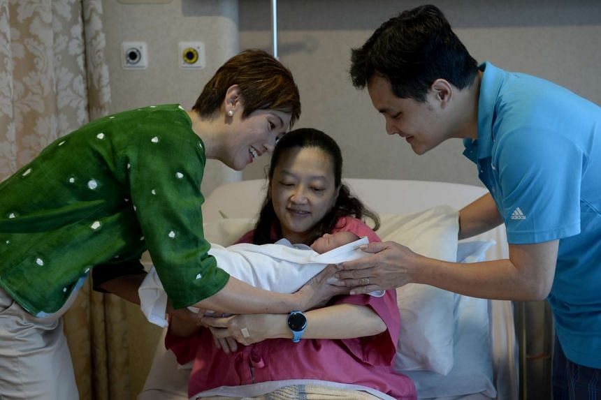 Senior Minister of State Josephine Teo (left) speaks to Tee Bee Ling and Shaun Soong, the parents of newborn baby Ansley at KK Women's and Children's Hospital on Jan 1, 2016.