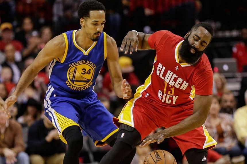 Shaun Livingston #34 of the Golden State Warriors reaches in to knock the ball away from James Harden #13 of the Houston Rockets.