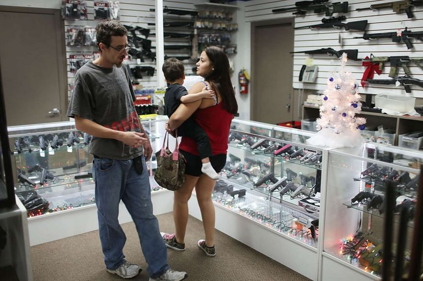 Kevin and Melissa Sherin shop for a Christmas gift, child in arms, at the National Armory gun store on Dec 23 in Pompano Beach, Florida in the US.