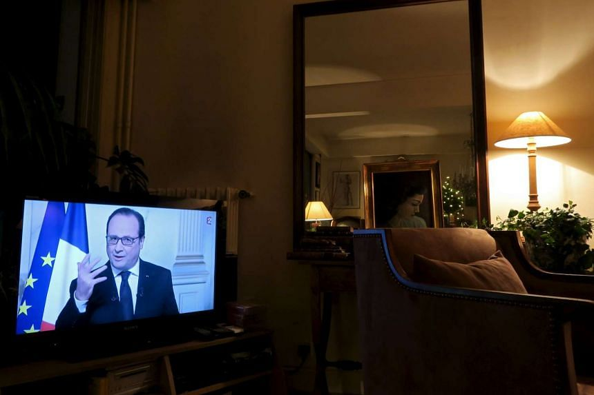 French President Francois Hollande, seen on a television screen in a living room in Asnieres, France as he gives his New Year speech in a pre-recorded presentation at the Elysee Palace.
