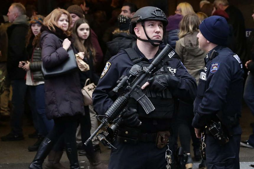 A member of the New York City Police department's Hercules team patrols in Times Square as crowds gather for New Year's Eve celebrations.