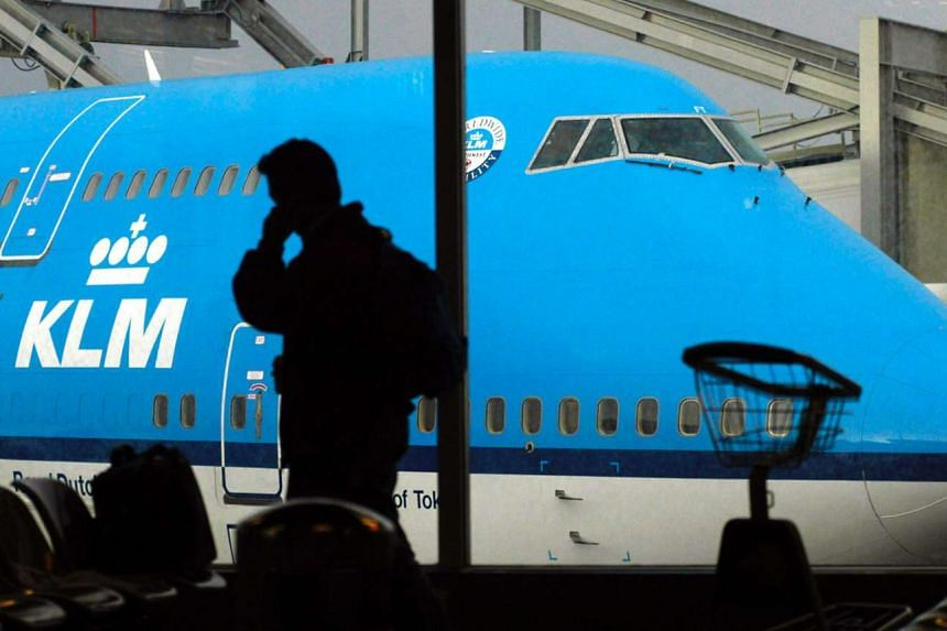 Passengers prepare to board a KLM flight at Schiphol airport, near Amsterdam in a file photo.