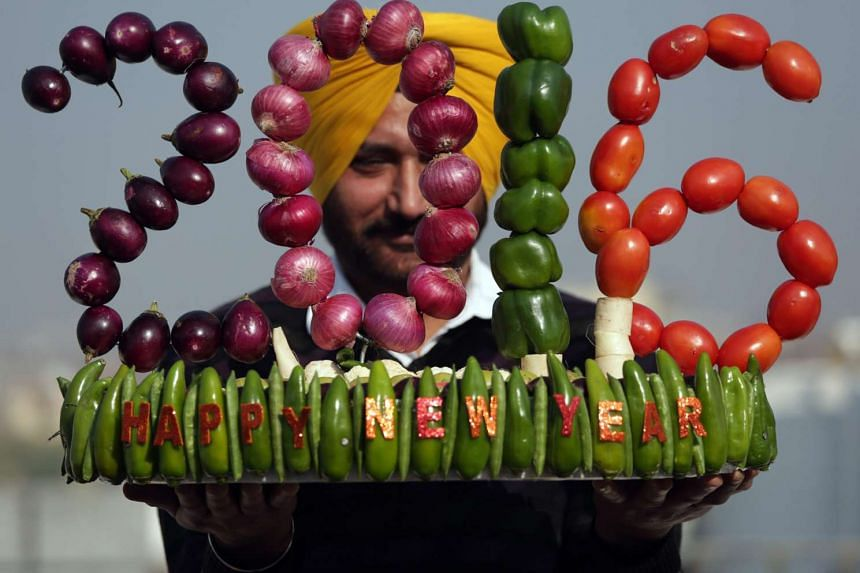 Indian artist Harwinder Singh Gill displaying his new artwork made with vegetables on New Year's Eve in Amritsar, India. A dental hygienist by profession, Mr Gill made the sculpture to wish everyone a prosperous new year.
