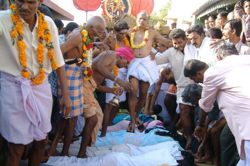 A priest wearing sandals with nails steps over devotees at a Tamil Nadu temple in a file photo.