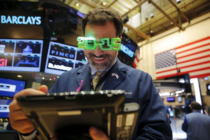 A trader wears plastic glasses to celebrate the last trading day of 2015.