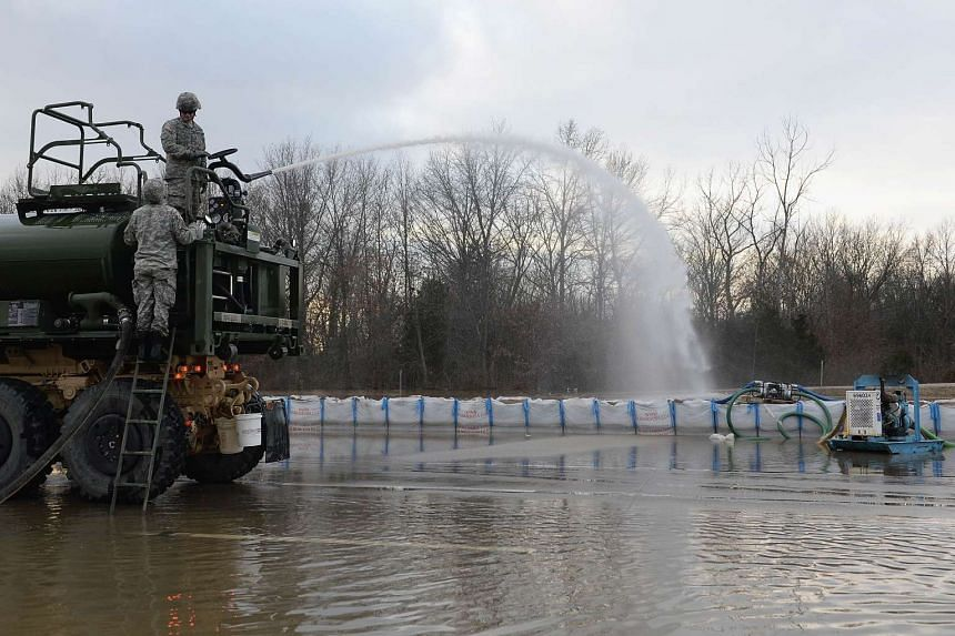 A member of the Missouri National Guard pumping water off a pavement on Dec 31, 2015.