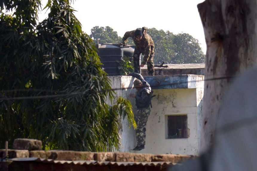 Indian security personnel position themselves on a rooftop at the airforce base during the attack.