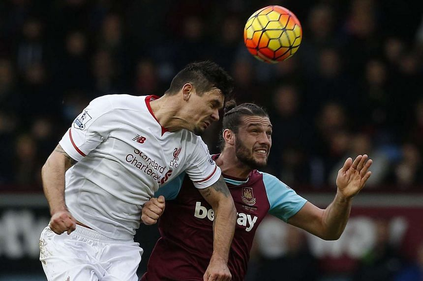 West Ham United's Andy Carroll vies in the air with Liverpool's Dejan Lovren during the match.