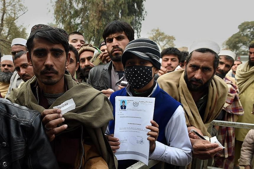 Afghan refugees gathering to renew their Proof of Registration cards at a centre in Peshawar, Pakistan, on New Year's Eve. Hundreds of thousands of people fled Afghanistan during the last three decades of war, with the majority of them taking refuge