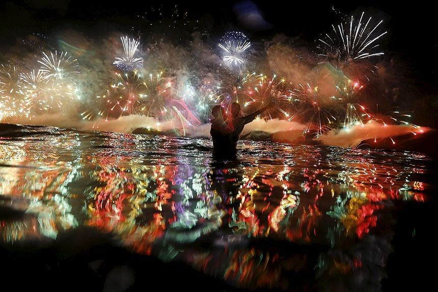 Fireworks going off over the Copacabana beach during New Year celebrations in Rio de Janeiro, Brazil, yesterday. Indonesians releasing sky lanterns to mark the new year during celebrations in Magelang, Central Java, yesterday. It's almost a tradition