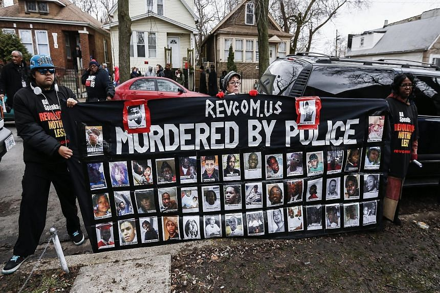 A banner showing photographs of Mr Quintonio LeGrier (top, left) and Ms Bettie Jones (top, right), along with pictures of other people shot and killed by Chicago police, at a vigil outside the location where Chicago cops were called to a domestic dis