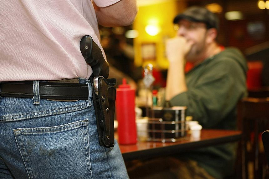 A handgun being openly carried in a hip holster in an American public eatery. More than 40 US states allow some form of open carry of firearms, with a pro-gun activist (far left) marching in support of such open-carry displays at a rally in Austin, T