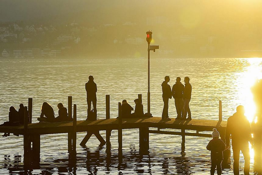 (Left) People taking advantage of the unseasonably warm, springlike winter in Europe to take a stroll at Lake Zurich, in Switzerland. (Above) A flowering tree, an uncommon sight in December, at the Rignon Park in Turin, Italy.