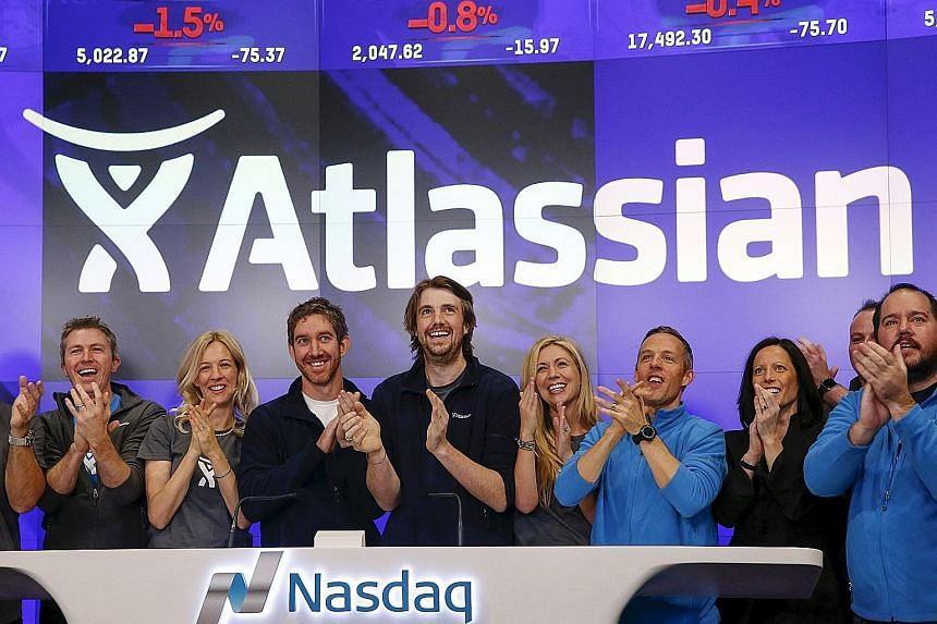 Atlassian co-founders and CEOs Mike Cannon-Brookes (centre) and Scott Farquhar (third from left) at the company's stock debut on Nasdaq on Dec 10. Public investors were willing to pay up for its shares after the company pitched its attractive track r