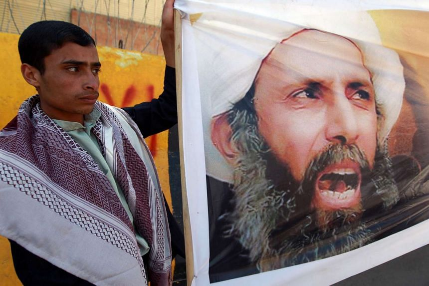 A man in Yemen protests the death sentence against Nimr (portrait) outside the Saudi embassy in Yemen's Sanaa in a file photo.
