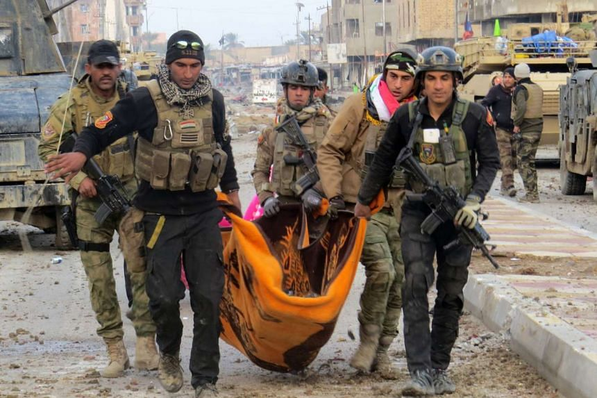 Iraqi troops carry the body of a comrade amid battles with ISIS militants as they try to secure Ramadi neighbourhoods.