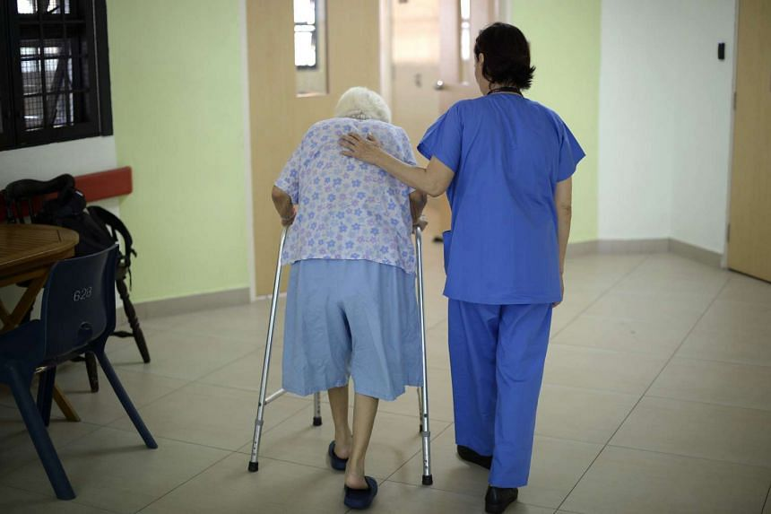 A nurse helping an elderly patient at Institute of Mental Health (IMH).