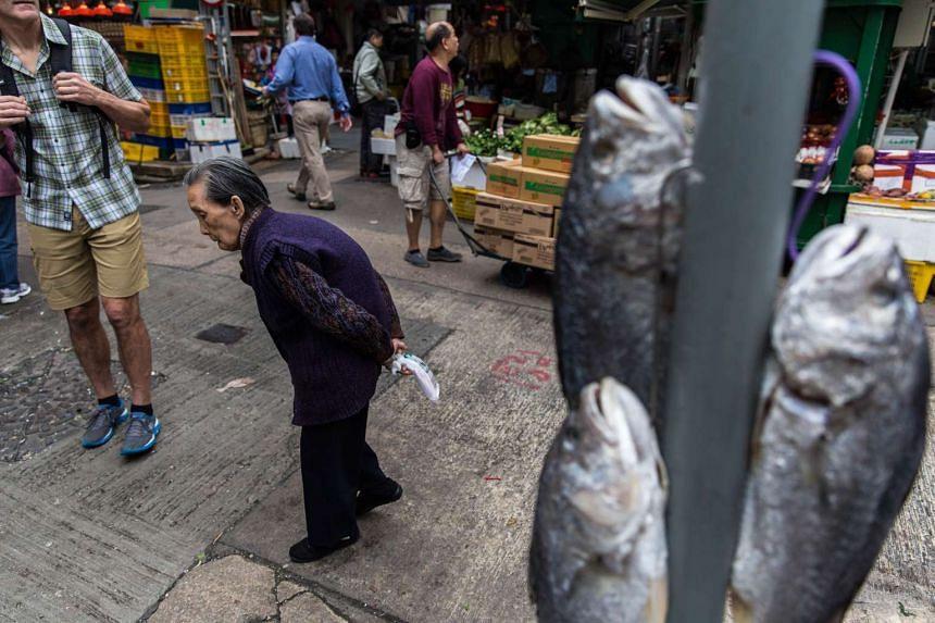 An elderly woman walks past a signpost near Graham Street in Hong Kong.