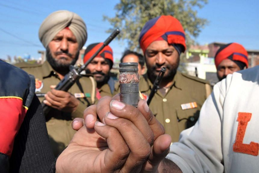 Indian policemen holding an object suspected to be from ammunition outside the Air Force base in Pathankot, India .