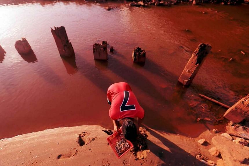 Red water is seen in Sungai Balok in Kuantan, Pahang, after heavy rains caused run-off from bauxite mines to wash into the waters.