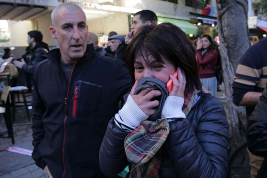 A woman reacts at the scene of an attack by an unidentified gunman in Tel Aviv.