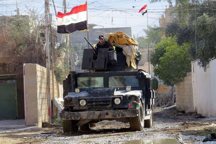 Iraqi pro-government forces drive a military vehicle during battles with Islamic State (IS) group jihadists in Ramadi.