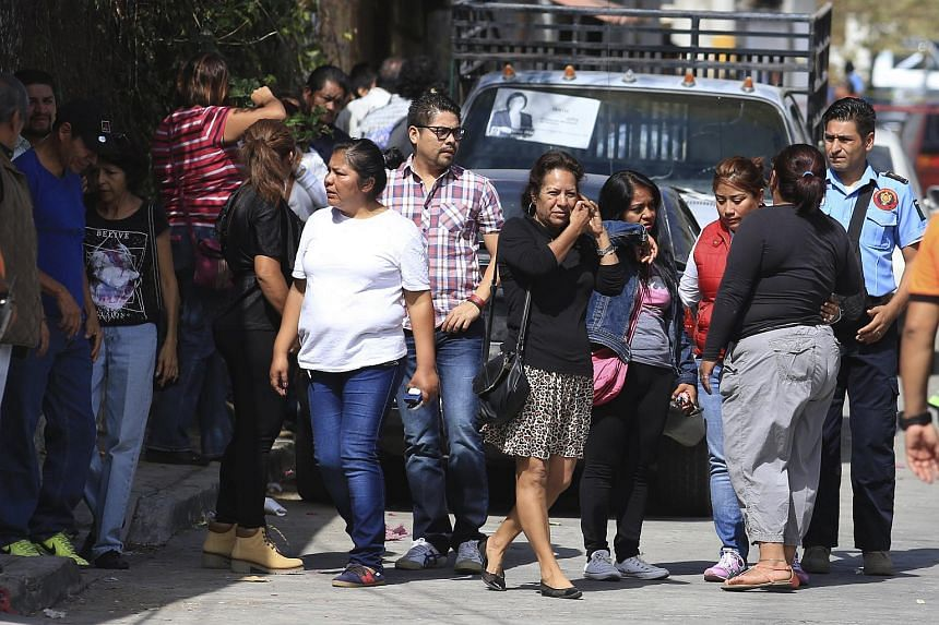 Residents react next to a crime scene where newly elected mayor Gisela Mota was attacked at her home by four armed gunmen.