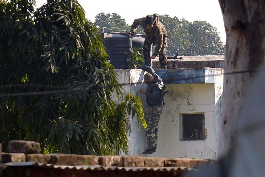 Indian security officers searching for gunmen who infiltrated an air force base in Pathankot yesterday. The operation to secure the base ended 14 hours after the militants, said to be from the Pakistan-based Jaish-e- Mohammed group, began the attack.