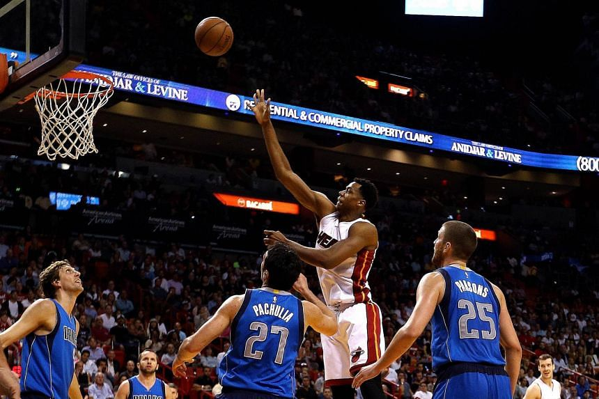 Miami Heat centre Hassan Whiteside driving to the basket past Dallas Mavericks centre Zaza Pachulia and small forward Chandler Parsons during the second half of their NBA game. Miami, who were never troubled, won the game 106-82.