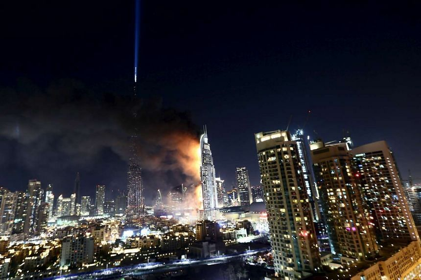 The hotel is seen engulfed by fire near the Burj Khalifa, the tallest building in the world.
