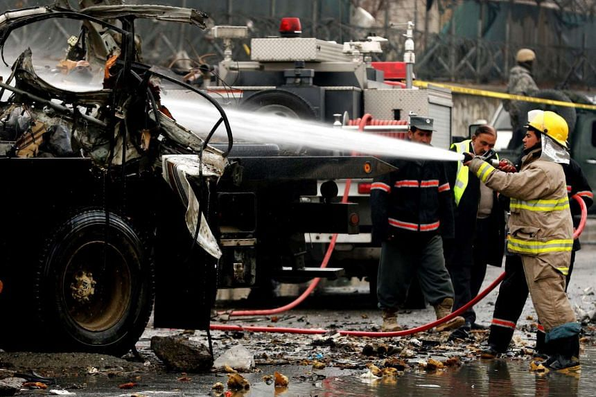 Firefighters cleaning the scene of a suicide bombing near Kabul airport on Jan 4, 2016.
