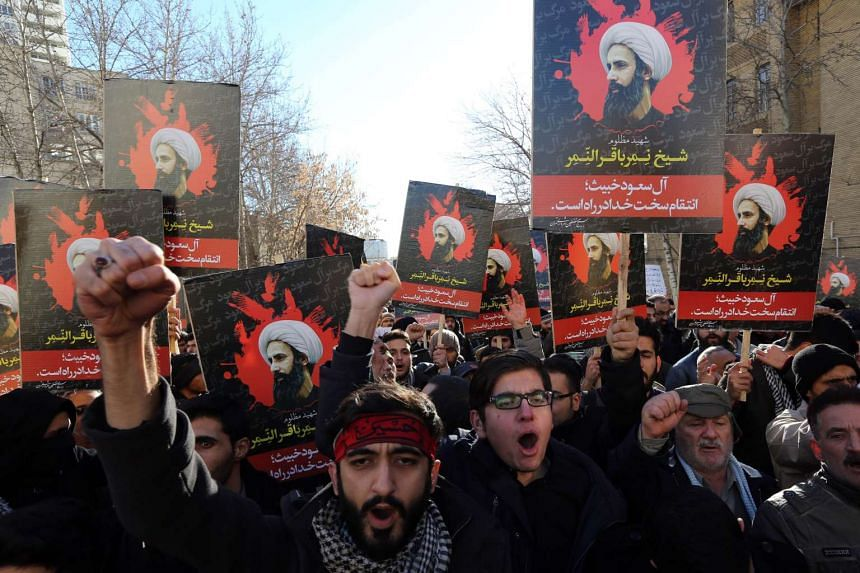 Iranian men hold portraits of prominent Shiite Muslim cleric Nimr al-Nimr during a demonstration on Jan 3, 2016, outside the Saudi embassy in Teheran.