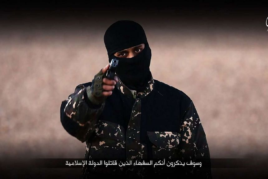 """A screengrab from a video, allegedly by ISIS, showing a fighter speaking in English before he and four others executed five """"spies""""."""