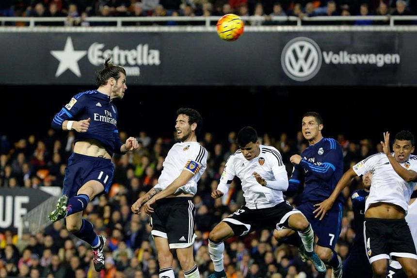 Real Madrid's Gareth Bale (left) heading the ball to score against Valencia on Jan 3, 2016.