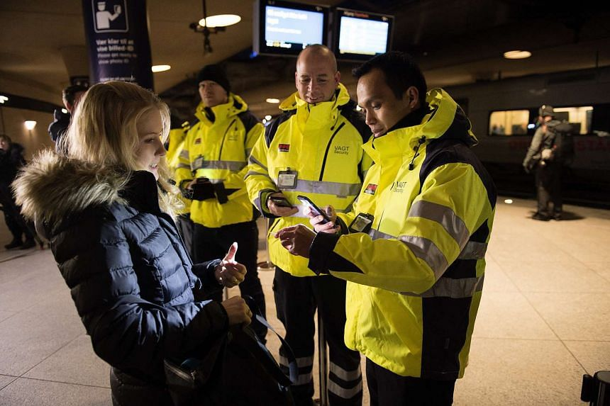 Security staff check a traveller's identification at Kastrups train station outside Copenhagen, Denmark on Jan  4, 2016.