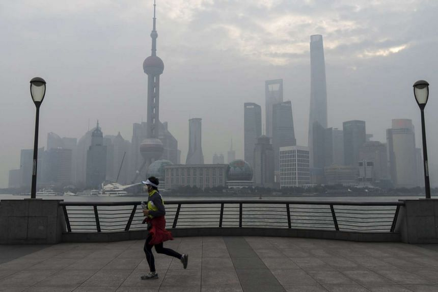 A jogger runs along the bund near the Huangpu river across the Pudong New Financial district, amid heavy smog in Shanghai.