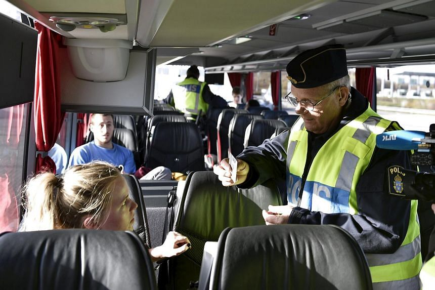 A police officer checks passports inside a bus at Lernacken, on the Swedish side of the Oresund strait.