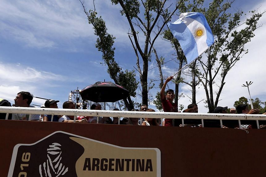 A boy waves an Argentine national flag during the departure ceremony of the 2016 Dakar Rally in Argentina on Jan 2.