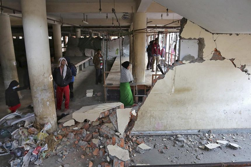 People look at a damaged building at a market place after an earthquake in Imphal, India on Jan 4.