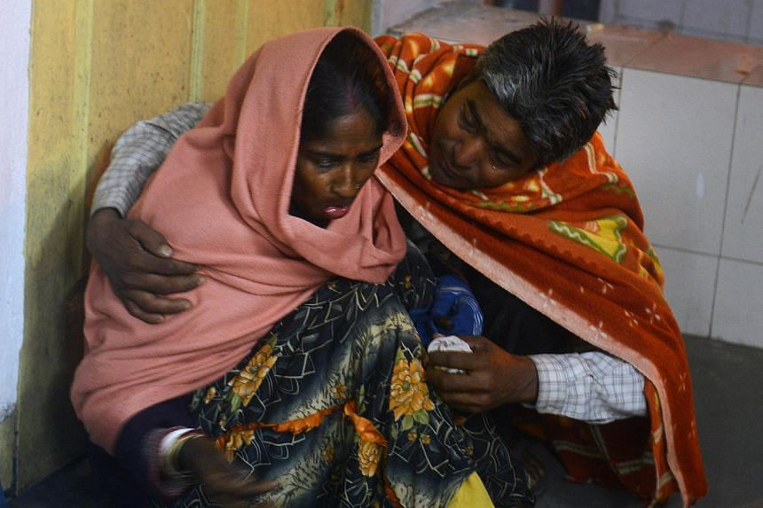 An injured Indian woman is comforted by her husband as she waits for treatment at Siliguri Hospital following an earthquake in Siliguri on Jan 4.