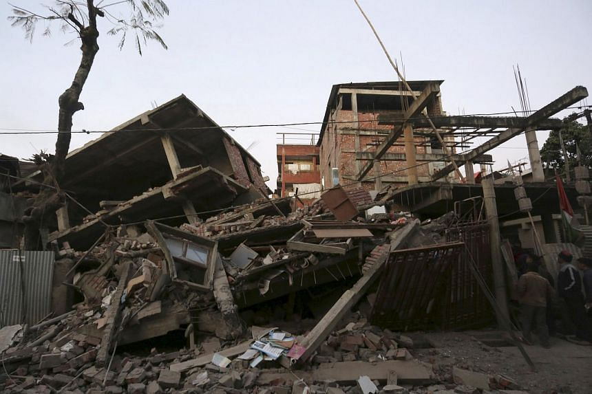 People look at damaged residential houses after an earthquake in Imphal, India on Jan 4.