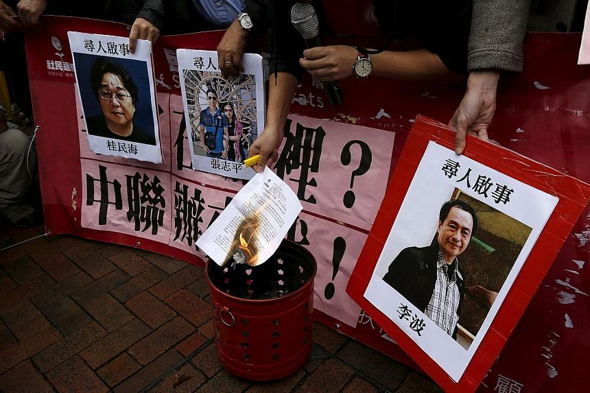 A demonstrator burning a letter next to pictures of missing people linked to a Hong Kong bookstore during a protest outside China's representative office yesterday. The photo on the right is of bookseller Lee Bo.