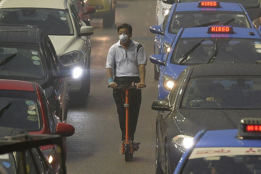 A plane taking off at the haze-hit Phuket International Airport in October. Some travellers who faced flight disruptions due to the haze have found they cannot make claims under their travel insurance policies. A man on an electric scooter wearing a